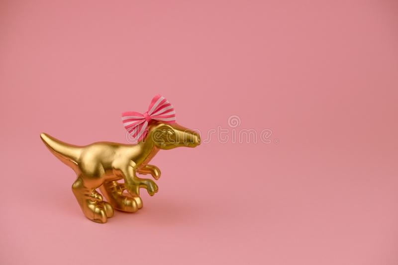 Golden girl dinosaur toy with festive bow on a sift pink background with copy space. Cute golden girl dinosaur toy with festive bow on a sift pink background stock photo
