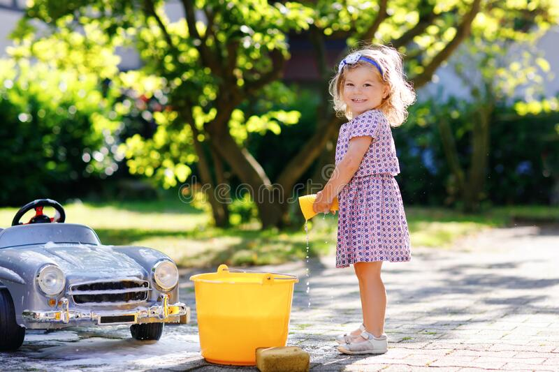 Cute gorgeous toddler girl washing big old toy car in summer garden, outdoors. Happy healthy little child cleaning car. With soap and water, having fun with stock photos