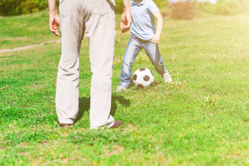 Cute grandchild and grandparent playing football together royalty free stock images