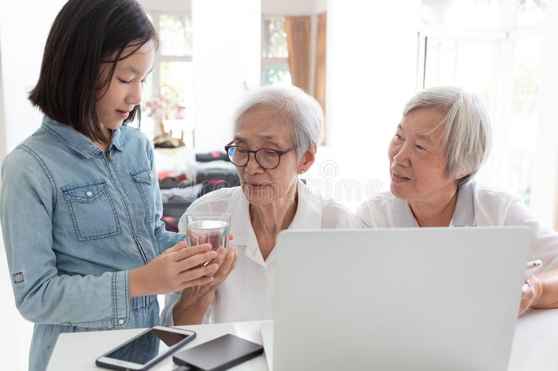 Cute granddaughter giving or serving cups of water for grandmother to drink,Happy two senior asian woman,sisters or friends royalty free stock photos