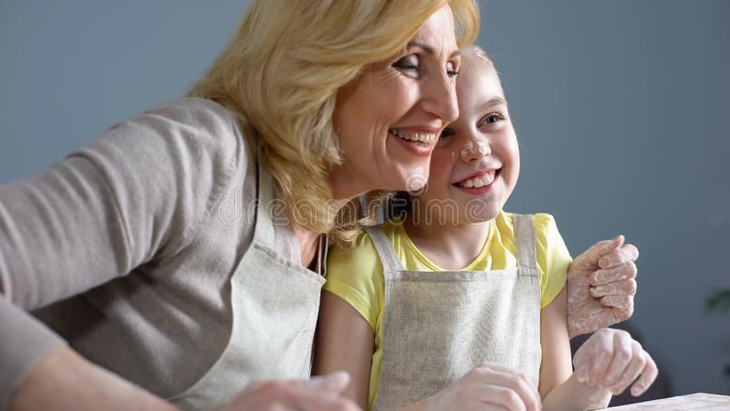 Cute granddaughter and her grandmother laughing and hugging while baking, family royalty free stock images