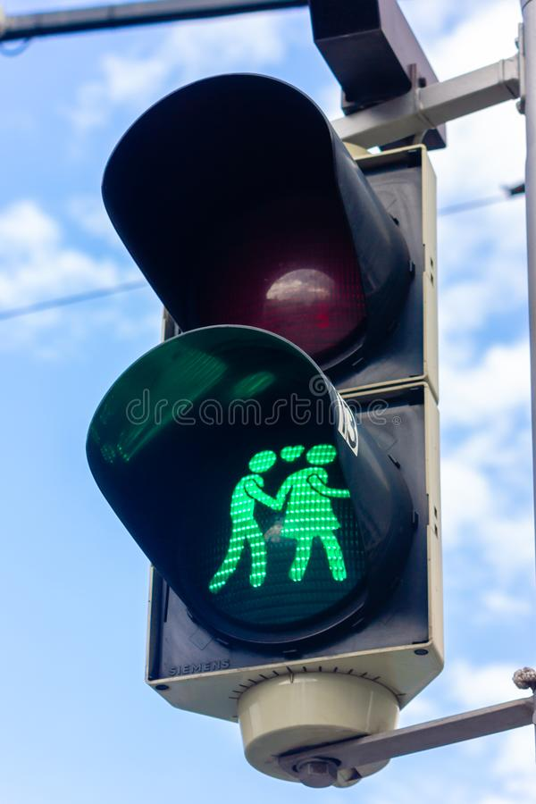 Cute, green pedestrian light with couple in Vienna, Austria. Blue sky with clouds stock images