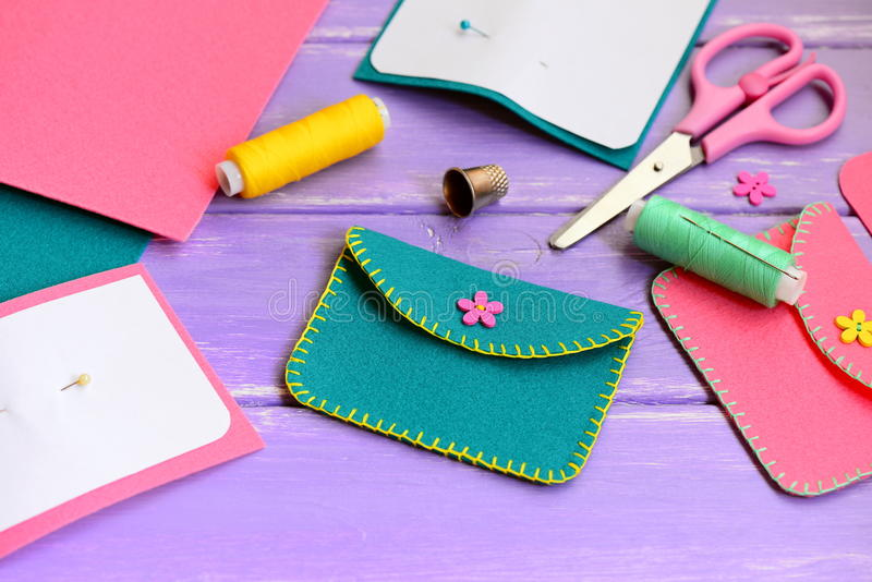 Cute green and pink felt purses with flower wooden buttons. Scissors, thread, needle, thimble, paper templates on a wooden table. Purse sewing pattern. Purse royalty free stock photos