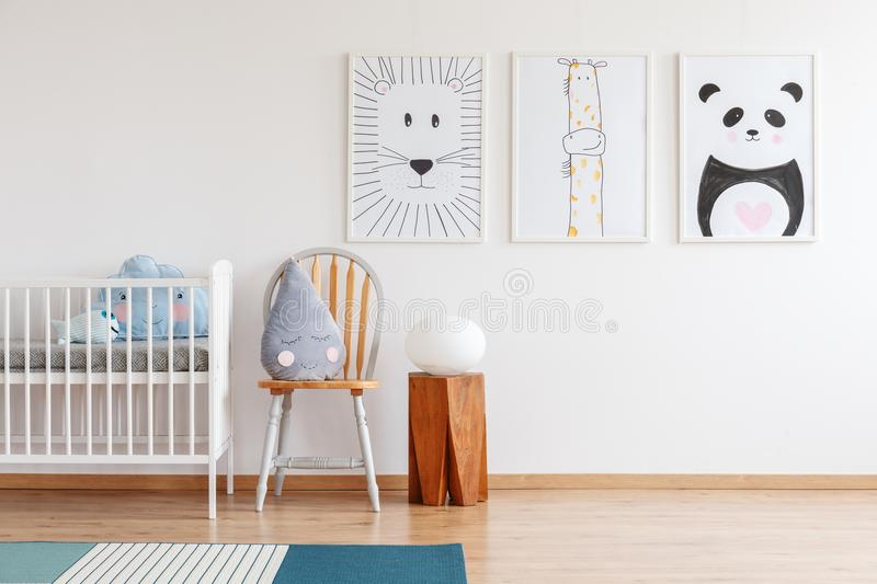 Raindrop shaped cushion. Cute grey raindrop shaped cushion placed on wooden chair standing next to white crib in bright baby room interior stock photography