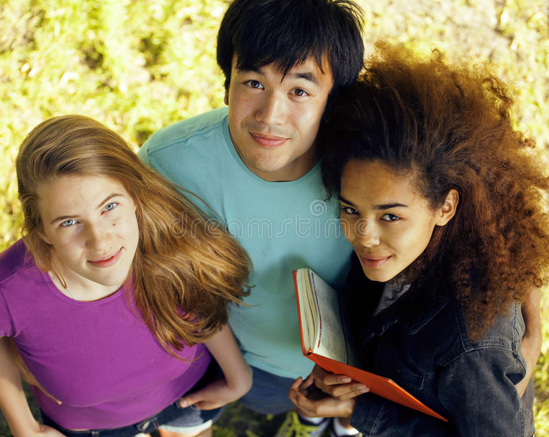 Cute group of teenages at the building of university with books huggings, diversity nations. Having lunch stock image