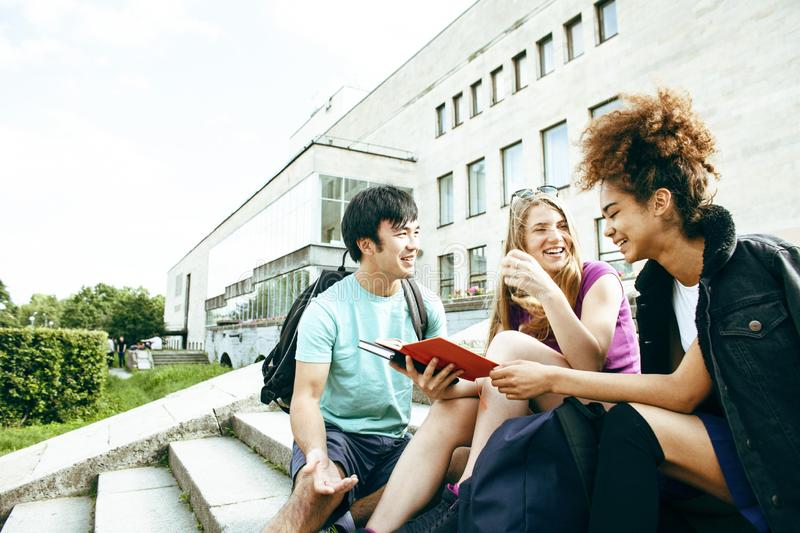Cute group of teenages at the building of university with books huggings, diversity nations students lifestyle. Cute group of teenages at the building of royalty free stock photo