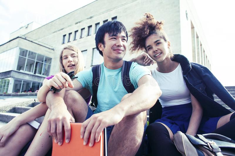 Cute group of teenages at the building of university with books huggings, diversity nations real students lifestyle royalty free stock images