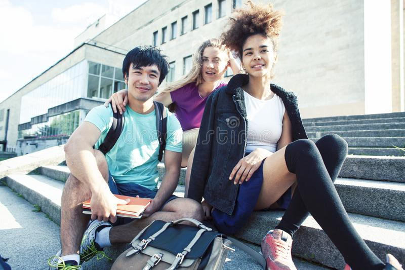 Cute group of teenages at the building of university with books huggings, diversity nations real students lifestyle royalty free stock photo