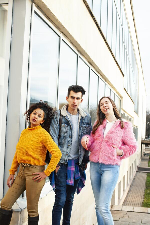 Cute group of teenages at the building of university with books huggings, diversity nations real students lifestyle royalty free stock photography