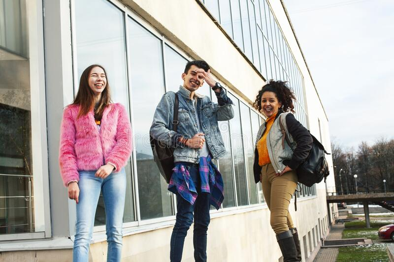 Cute group of teenages at the building of university with books huggings, diversity nations real students lifestyle stock image