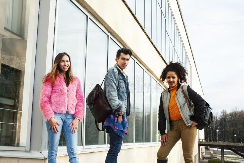 Cute group of teenages at the building of university with books huggings, diversity nations real students lifestyle royalty free stock photos