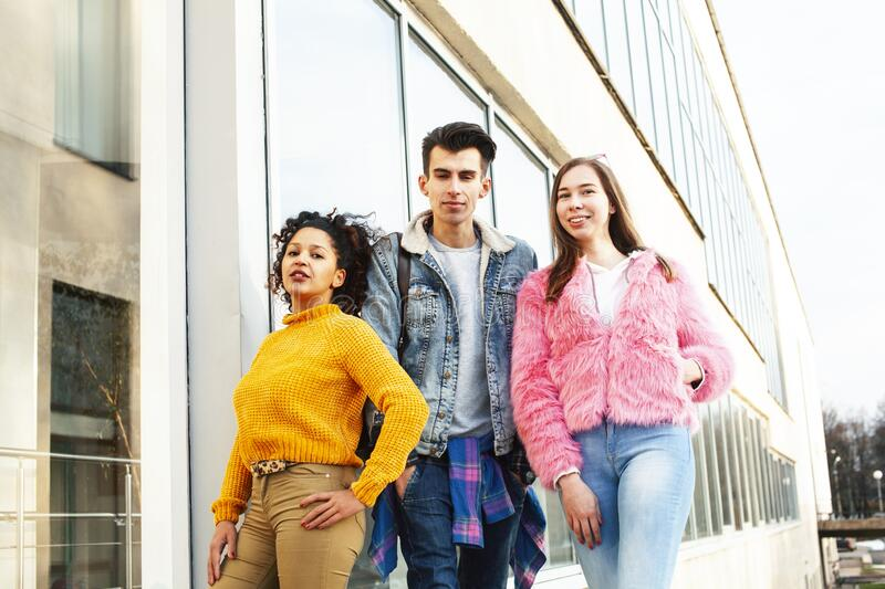 Cute group of teenages at the building of university with books huggings, diversity nations real students lifestyle stock photography
