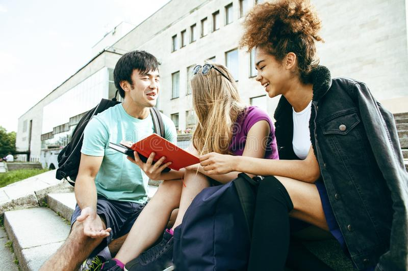 Cute group of teenages at the building of university with books huggings, diversity nations students lifestyle. Cute group of teenages at the building of royalty free stock photography