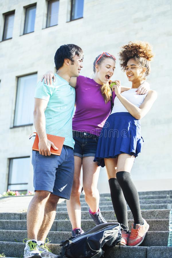 Cute group of teenages at the building of university with books huggings, diversity nations students lifestyle. Cute group of teenages at the building of stock image