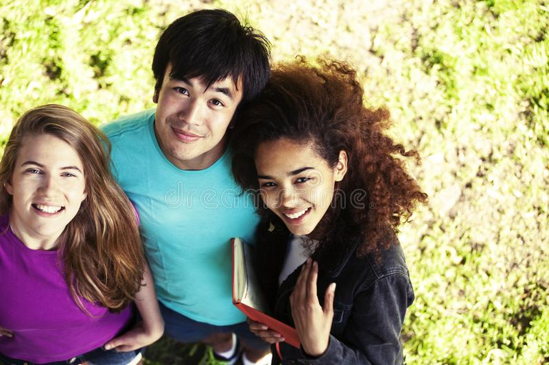 Cute group of teenages in green park at summer with books huggings, diversity nations real students lifestyle royalty free stock photography
