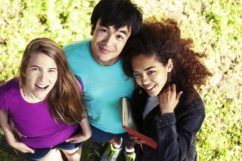 Cute group of teenages in green park at summer with books huggings, diversity nations real students lifestyle royalty free stock photo