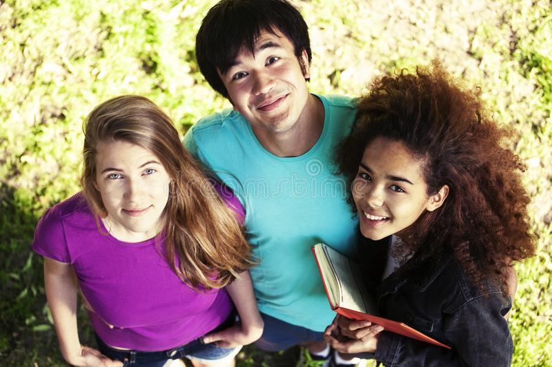 Cute group of teenages in green park at summer with books huggings, diversity nations real students lifestyle stock photography