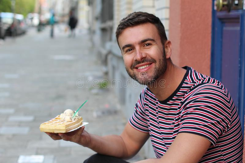 Cute guy eating a waffle in Brussels, Belgium royalty free stock photo