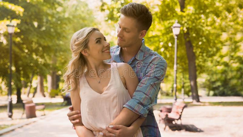 Cute guy and girl looking at each other with love tenderly, cuddling in park stock images