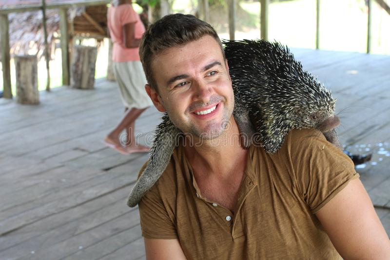 Cute guy playing with a Brazilian porcupine royalty free stock photos