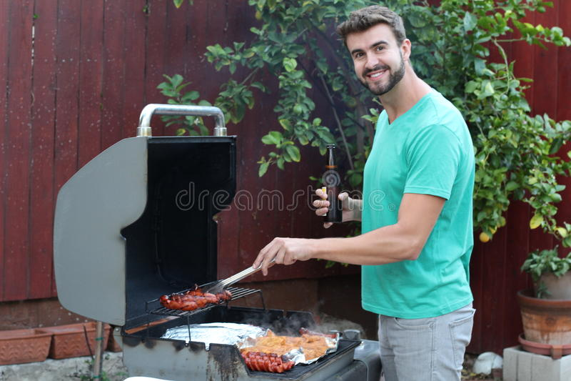 Cute guy smiling and cooking on the barbecue grill.  royalty free stock photography