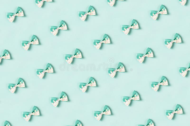 Cute hair bow pattern on bright background, flat lay. Colorful hair bow pattern on pastel blue background, flat lay, top view stock photo