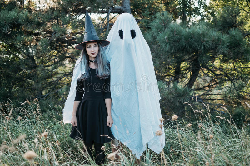 Cute Halloween couple. Ghost with young witch walking in autumn forest stock photo