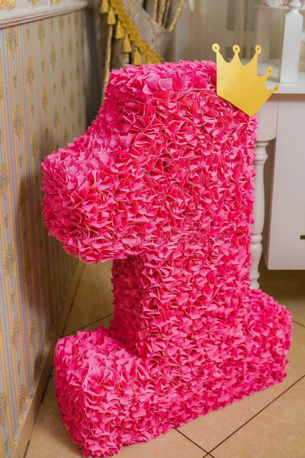Cute handmade decoration for birthday party. Big sweet pink figure 1 decorated with yellow paper crown of princess stands on floor at home or restaurant royalty free stock photos