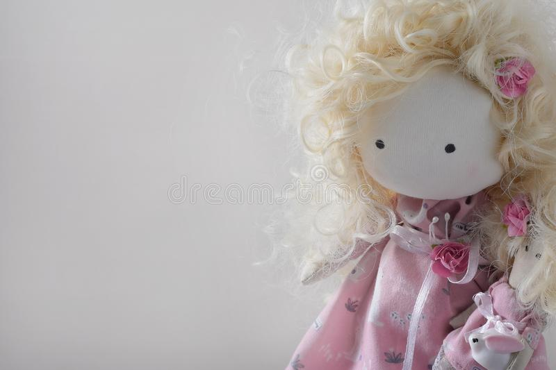 Cute handmade doll with blond curly-hair closeup with copyspace royalty free stock photos