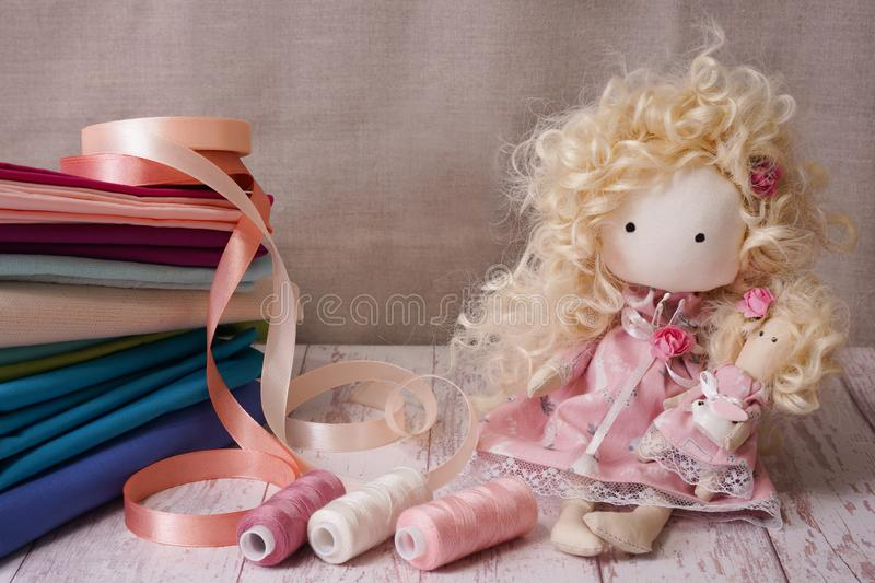Cute handmade doll on a wooden table near colorful fabrics, knitted lace, pastel ribbons stock photo