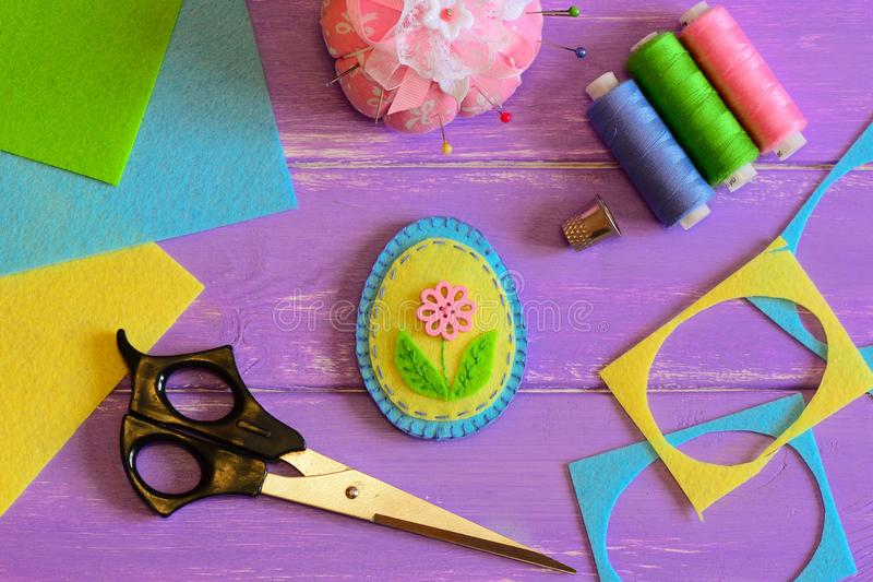 Cute handmade felt Easter egg, colored thread set, scissors, thimble, pin cushion, felt scrap and sheets on a purple wooden table. Easter crafts for kids. Fun royalty free stock photos