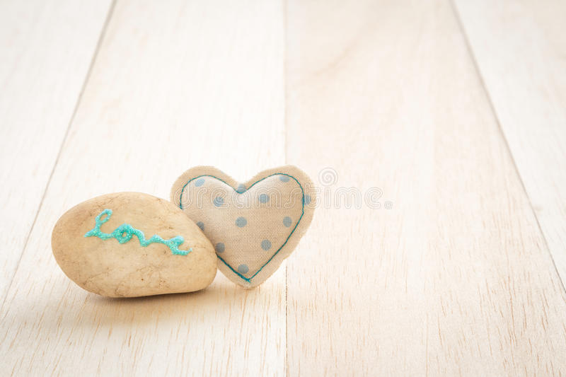 Cute handmade heart and glitter love word on stone. Cute heart handmade crafts from blue polka dot cotton cloth with glitter love word on stone place on wood stock image