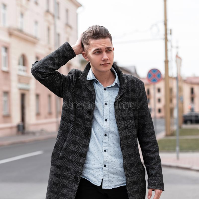 Cute handsome young man in a stylish jacket in a vintage shirt in trendy jeans with a fashionable hairstyle walks through the city. Streets on a warm spring day royalty free stock image