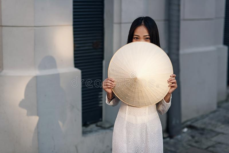 Cute happy asian girl dressed in Ao Dai dress closes half of her face with vietnamese conical hat. stock photos