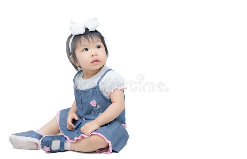 Cute happy asian little girl sitting on the floor, isolated stock image