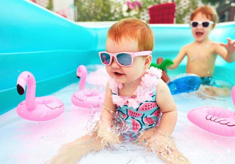 Cute happy baby girl having fun in kid pool, summer vacation royalty free stock photography