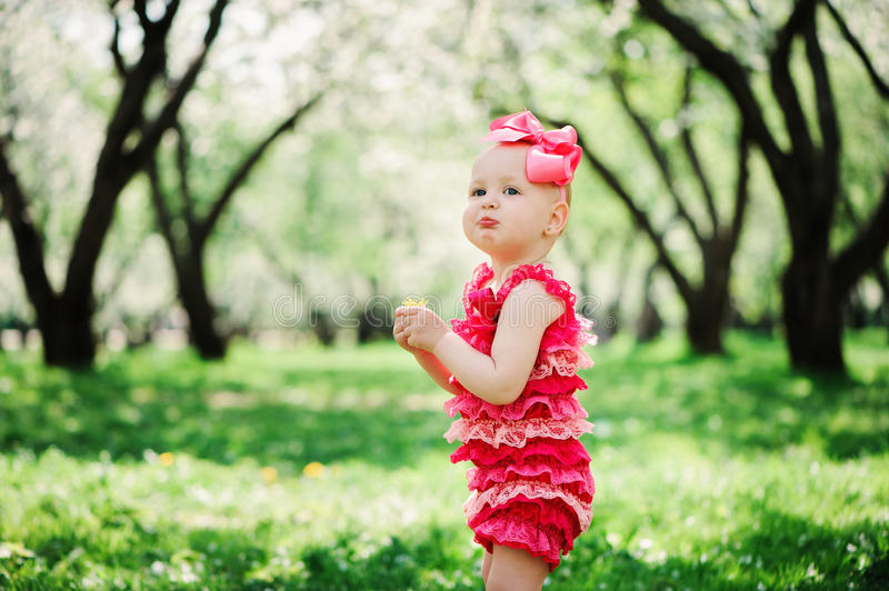 Cute happy baby girl in funny pink romper walking outdoor in spring garden royalty free stock images