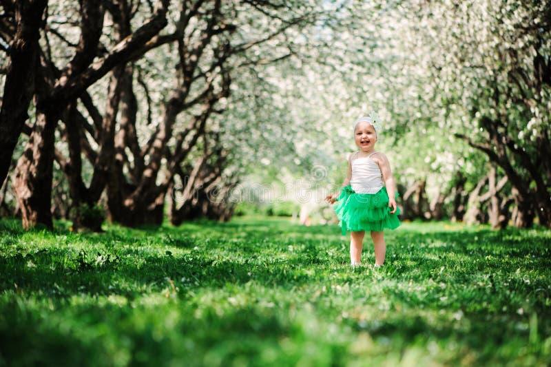 Cute happy baby girl in green tutu skirt walking outdoor in spring garden royalty free stock photos
