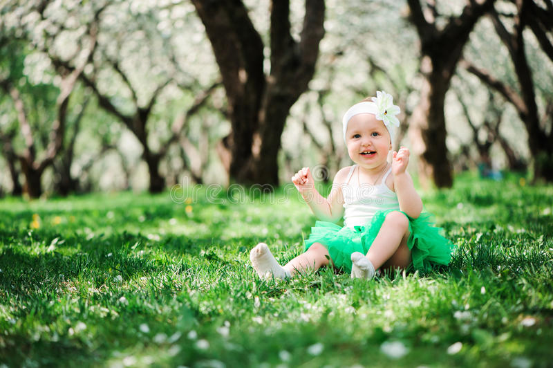 Cute happy baby girl in green tutu skirt walking outdoor in spring garden stock photos