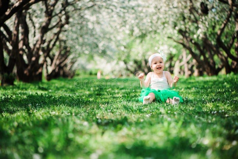 Cute happy baby girl in green tutu skirt walking outdoor in spring garden stock images