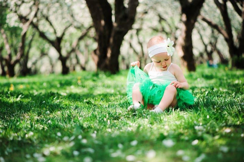Cute happy baby girl in green tutu skirt walking outdoor in spring garden royalty free stock image
