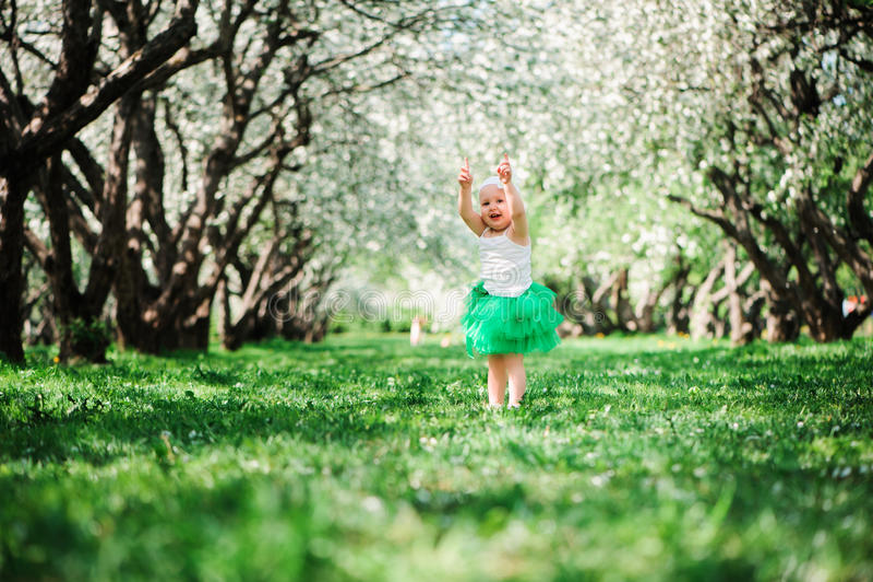 Cute happy baby girl in green tutu skirt walking outdoor in spring garden royalty free stock photo