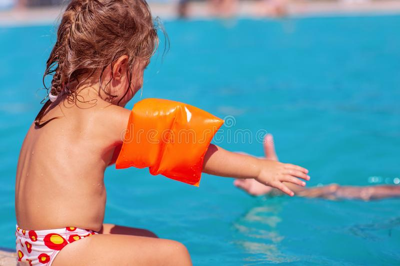 Cute baby girl learning swimming with inflatable armbands royalty free stock photography