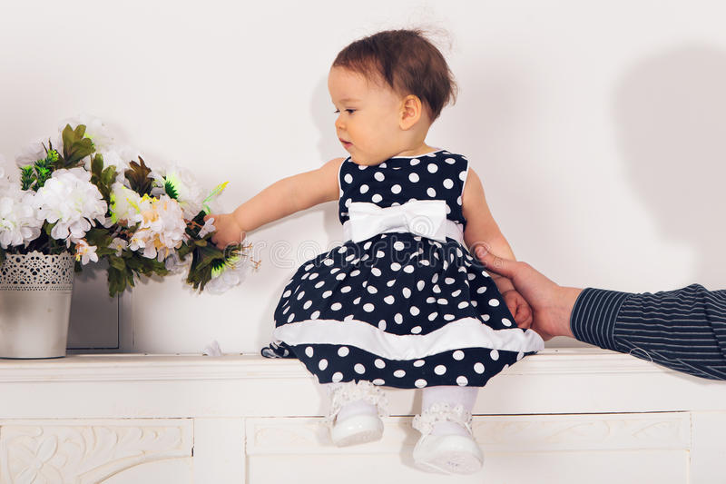 Cute happy baby girl wearing a dress playing with a bunch of beautiful big flowers in a vase in a white living room stock photo