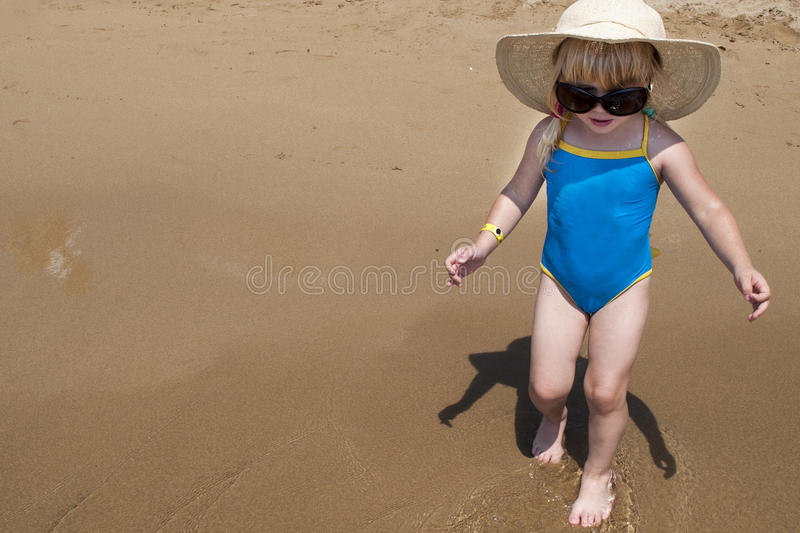 Cute happy baby girl wearing swimming suit, sun glasses, hat royalty free stock photography