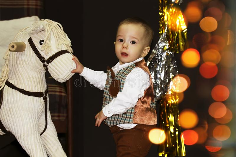 Cute happy baby near rocking horse in a decorated Christmas room with bokeh royalty free stock photography