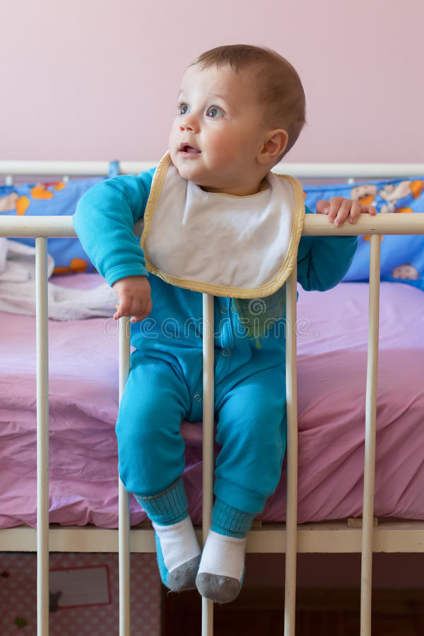 Cute happy baby sitting in crib.  royalty free stock photography
