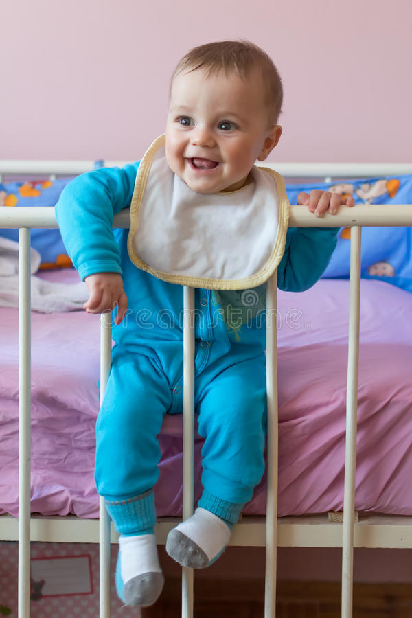 Cute happy baby sitting in crib.  stock photography