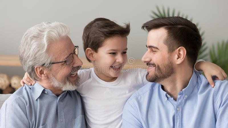 Cute happy boy grandson embracing young father and old grandfather. Cute happy little boy son grandson embracing young father and old elder grandfather laughing stock images