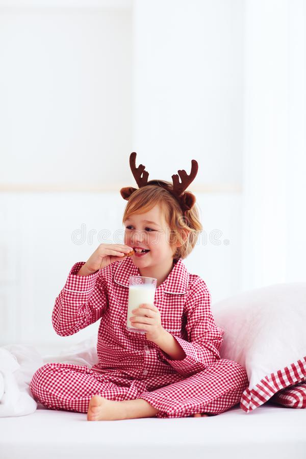 Cute happy boy, kid in traditional flannel pajamas sitting on the bed with glass of fresh milk and cookies, christmas holidays stock photo